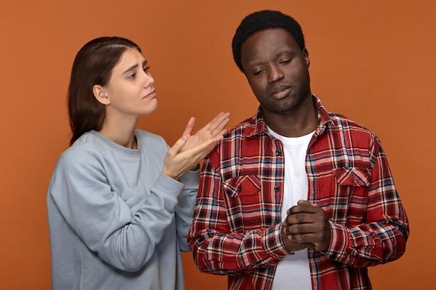 私を許してください。悲しげな表情で身振りで示す不幸な心配の若い白人女性は、彼女の気分を害した動揺した暗い肌の夫に許しを求めます。人と人間関係