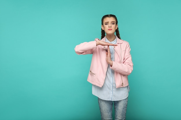 Please give me more time. portrait of beautiful cute girl standing with makeup and brown pigtail hairstyle in striped blue shirt pink jacket. indoor, studio shot isolated on blue or green background.