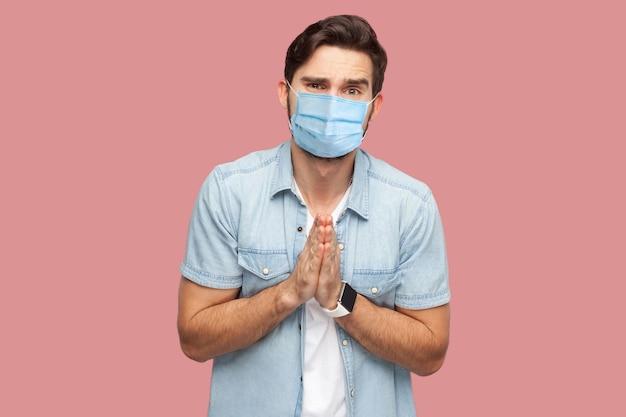 도와주세요, 아니면 용서해주세요. 파란 셔츠에 외과용 마스크를 쓰고 카메라를 보며 구걸하는 슬픈 희망적인 청년의 초상화. 실내 스튜디오 촬영, 분홍색 배경에 격리.