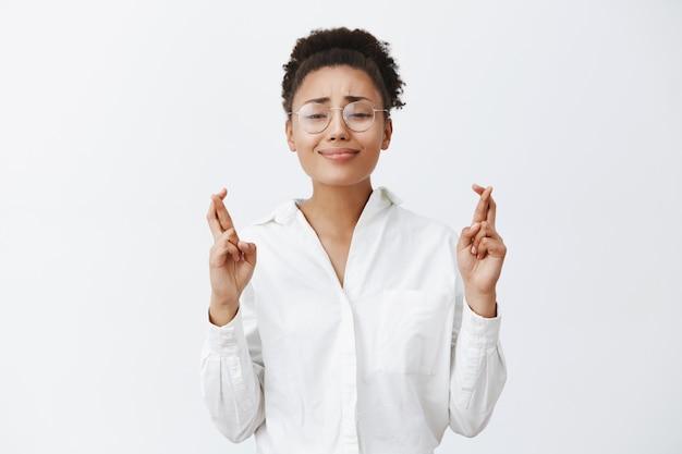 手伝ってください、お願いします。メガネとホワイトカラーのシャツを着た魅力的でキュートな黒肌の女性、指を組んで抱きしめながら笑顔を浮かべ、友人からお金を貸してくれるように祈って懇願する