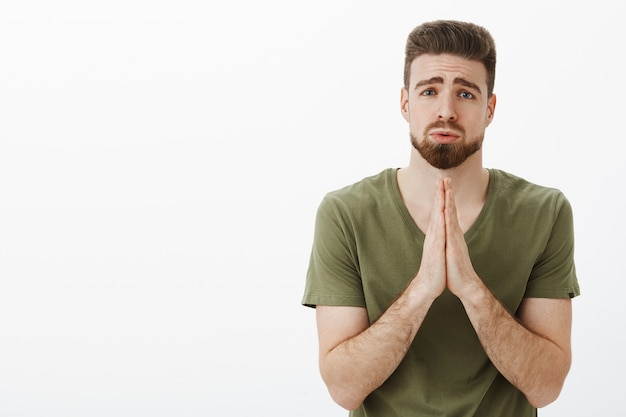 Please i beg you. portrait of cute charming bearded male in need holding hands in pray, supplicating pouting and frowning looking upset as asking favour or help hopefully over white wall