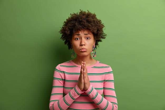お願いします、とても必要です。嘆願するような表情の悲しい暗い肌の女性、手のひらを一緒に握りしめ、助けを求めて祈って懇願し、必死に訴えかける表現をし、許可を求め、謝罪します