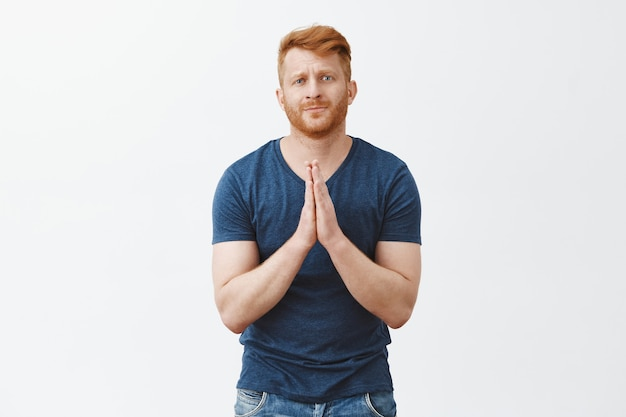 Please i really need your help. portrait of attractive and cute redhead bearded male in casual outfit, holding hands in pray and pursing lips while begging for favor or apology over gray wall