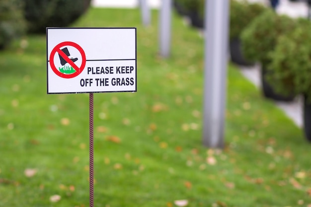 Please keep off the grass sign on green lawn grass blurred bokeh background on sunny summer day. city lifestyle and nature protection concept.