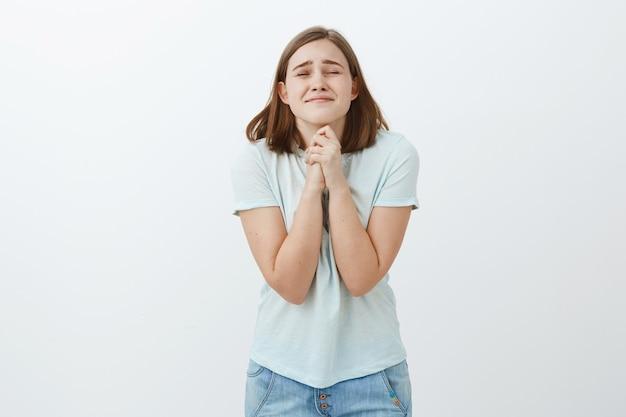 Per favore, fallo vero. speranzosa studentessa carina, ottimista e fedele, chiudendo gli occhi e stringendo le labbra intensamente stringendo le mani insieme vicino al corpo mentre esprime un desiderio o prega sul muro bianco