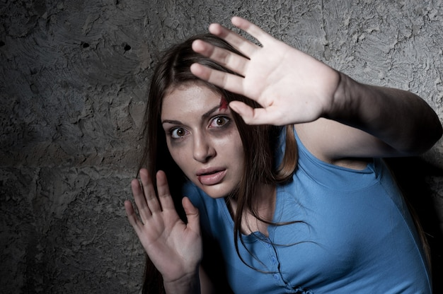 Please no! terrified young woman looking at camera and stretching out hand while leaning at the dark wall