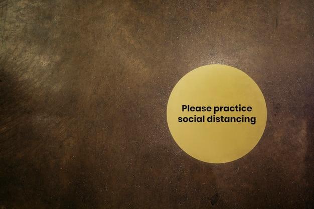 茶色の背景に社会的な距離の黄色い看板を練習してください