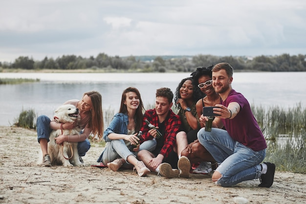 Пожалуйста, улыбнись. группа людей устраивает пикник на пляже. друзья веселятся в выходные.
