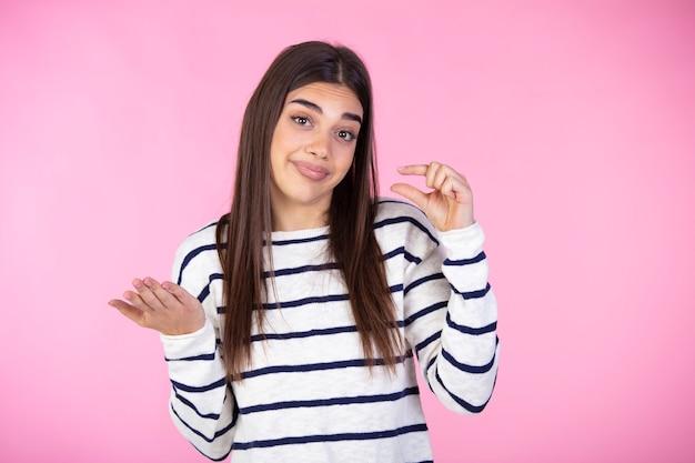 좀 더주세요. 작은 크기 또는 손가락으로 약간의 제스처를 보여주는 스웨터에 귀여운 소녀의 초상화