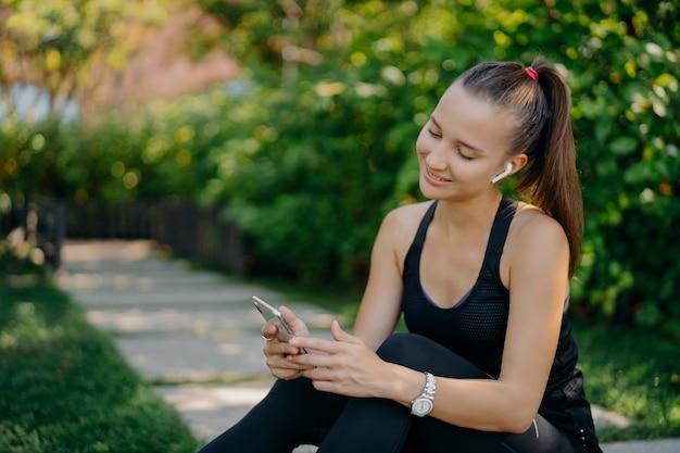 조랑말 꼬리를 가진 기뻐하는 활동적인 여성은 스마트 폰 장치에 집중된 낚시를 좋아하는 옷을 입고 무선 이어폰으로 음악을 듣고 인터넷을 탐색하며 야외 훈련을합니다. 건강한 라이프 스타일 컨셉