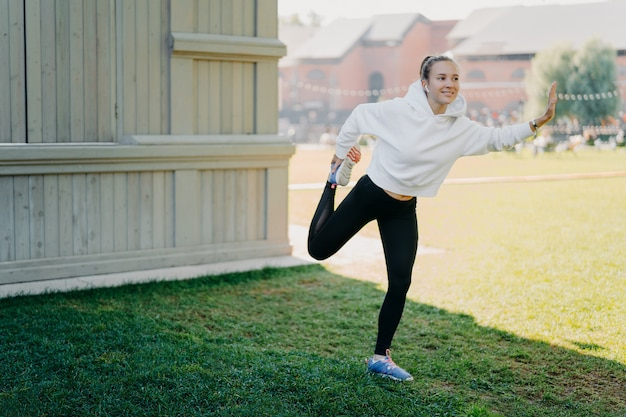 Pleased active young woman in hoodie and leggings prepares for running stratches and warms legs focused happily into distance listens music via earphones poses outdoors leads active lifestyle
