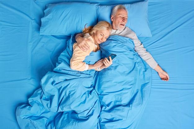 Довольная пристрастившаяся к современным технологиям женщина использует мобильный телефон в постели, получает объятия от спящего мужа, просматривает интернет перед сном. семейная пара среднего возраста отдыхает в уютной спальне.