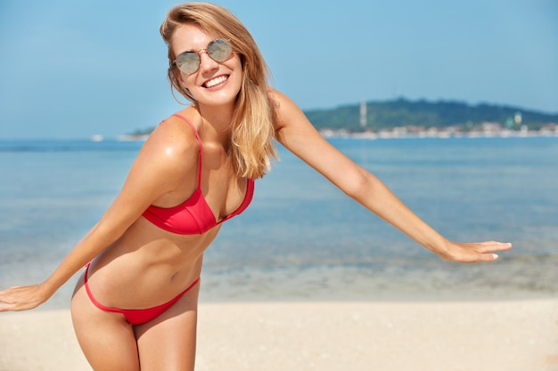 Довольная очаровательная женщина с счастливым выражением лица, загорелой здоровой кожей, позирует в красном купальнике на фоне моря, дышит морским воздухом, демонстрирует идеальную фигуру, наслаждается солнцем и голубым небом
