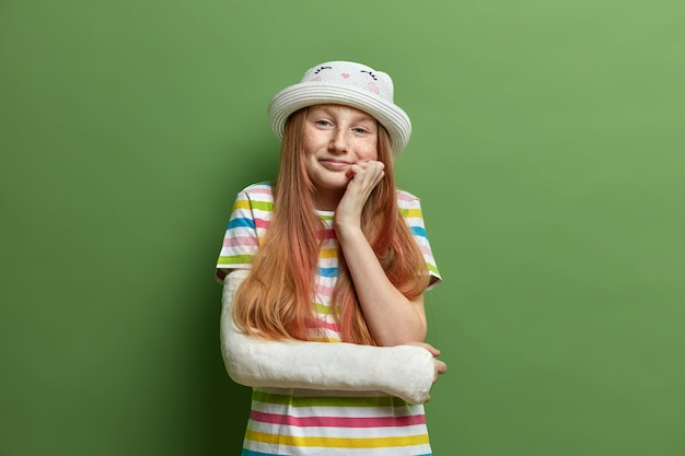 Pleased adorable preteen girl keeps hand under chin, has smiling expression, dressed in summer outfit, recovers after accident, has broken arm, wears cast after visiting surgeon