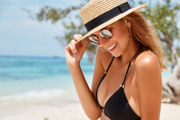 Pleased adorable young woman in trendy shades and summer hat, has positive smile on face, rests on coastline, enjoys sunny hot day, bathes in sun, has slim body. relaxed female tourist outdoor