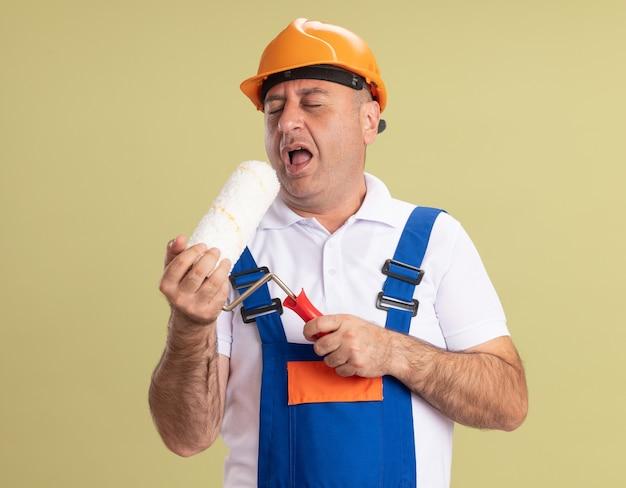 満足している大人のビルダーの男は、オリーブグリーンの壁に孤立して歌うふりをしてローラーブラシを保持します