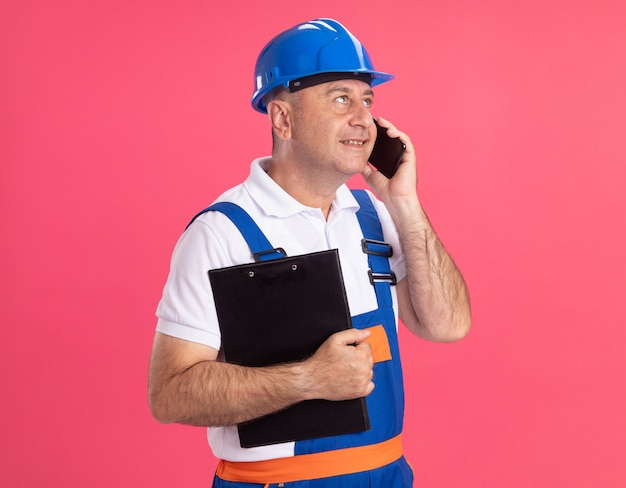 제복을 입은 기쁘게 성인 작성기 남자 클립 보드를 보유하고 분홍색 벽에 고립 된 측면을보고 전화 회담