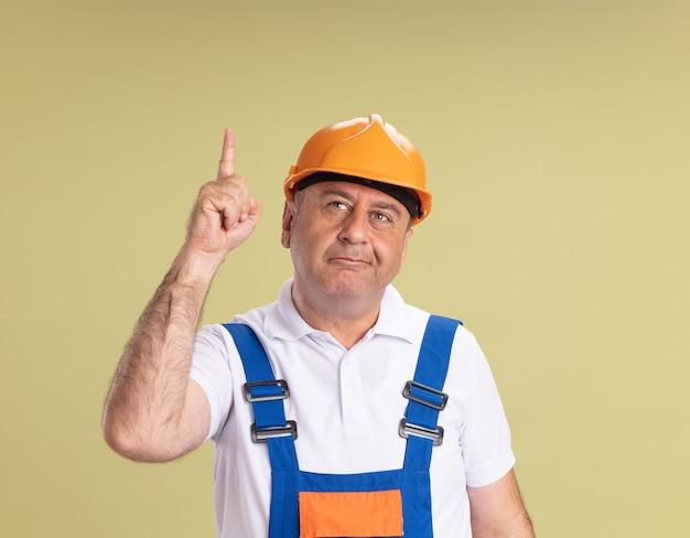 Довольный взрослый мужчина-строитель указывает на оливково-зеленый