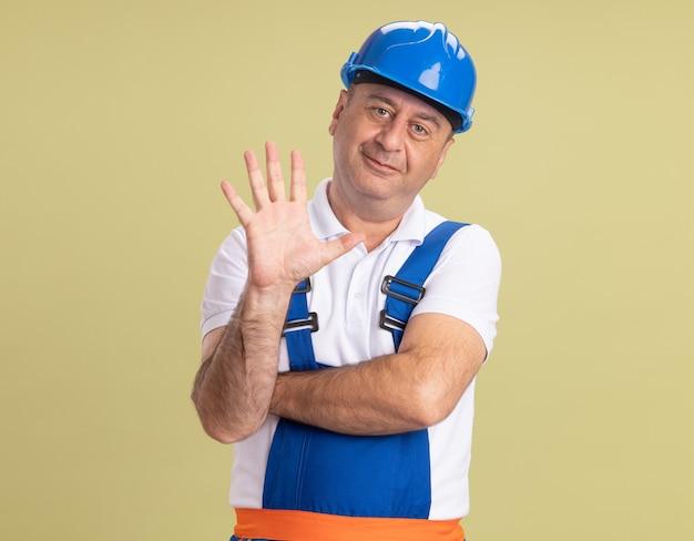 Uomo adulto soddisfatto del costruttore in gesti uniformi cinque isolati sulla parete verde oliva
