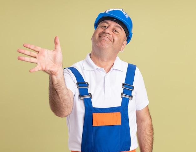 Uomo adulto soddisfatto del costruttore in uniforme che tiene la mano aperta su verde oliva