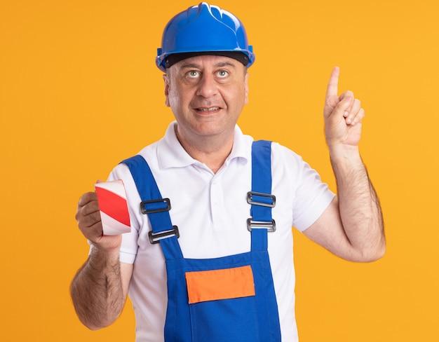 L'uomo adulto soddisfatto del costruttore in uniforme tiene la bocca delle coperture con del nastro adesivo e indica in alto isolato sulla parete arancione