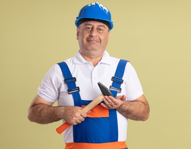 L'uomo adulto soddisfatto del costruttore in uniforme tiene il martello isolato sulla parete verde oliva