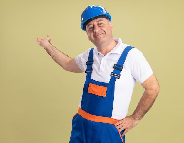 Uomo adulto soddisfatto del costruttore in punti uniformi indietro con la mano isolata sulla parete verde oliva