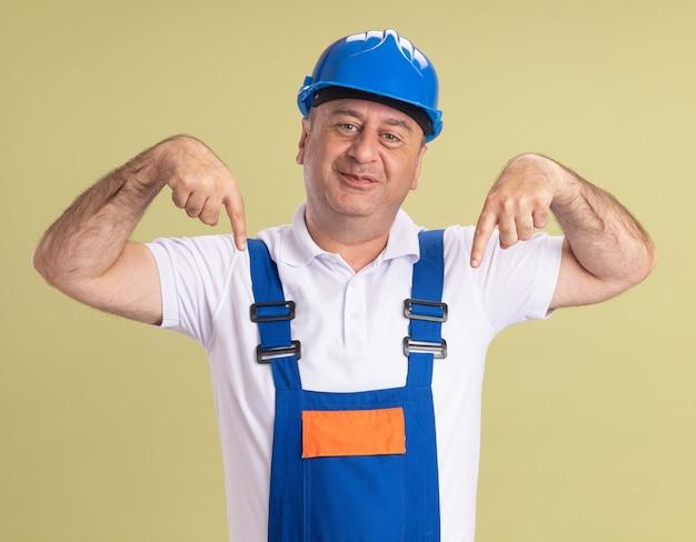 L'uomo adulto soddisfatto del costruttore in uniforme indica giù di due mani isolate sulla parete verde oliva