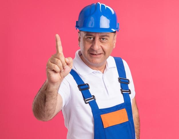 L'uomo adulto soddisfatto del costruttore in uniforme indica in alto isolato sulla parete rosa