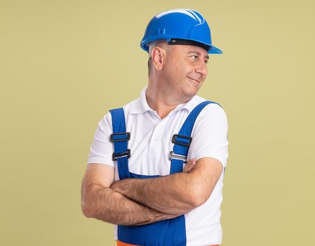 Felice uomo costruttore adulto in uniforme sta con le braccia incrociate guardando il lato isolato sulla parete verde oliva