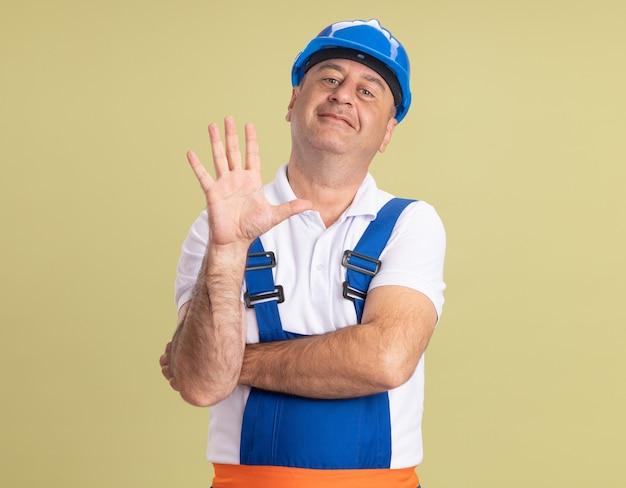 L'uomo adulto soddisfatto del costruttore in uniforme sta con la mano alzata isolata sulla parete verde oliva