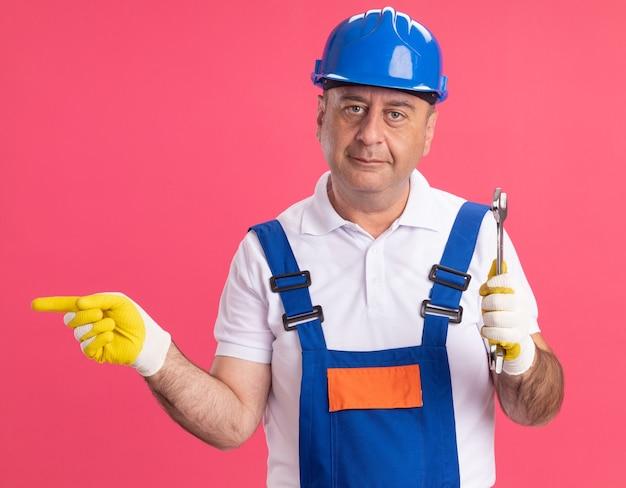 Felice adulto indoeuropeo costruttore uomo in uniforme che indossa guanti protettivi tiene chiave e punti a lato sul rosa