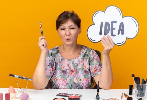 Piacevole donna caucasica adulta seduta al tavolo con strumenti per il trucco in possesso di bolla di idea e pennello per il trucco isolato sulla parete arancione con spazio di copia