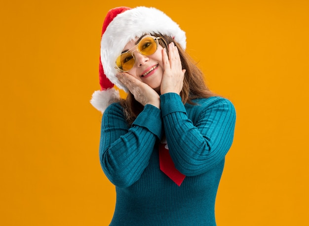 Pleased adult caucasian woman in sun glasses with santa hat and santa tie puts hands on face isolated on orange wall with copy space