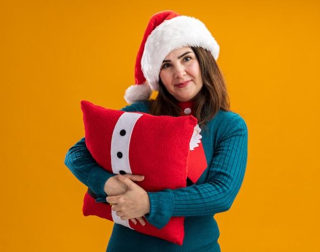 산타 모자와 산타 넥타이와 기쁘게 성인 백인 여자는 복사 공간 오렌지 벽에 고립 된 장식 베개를 안아