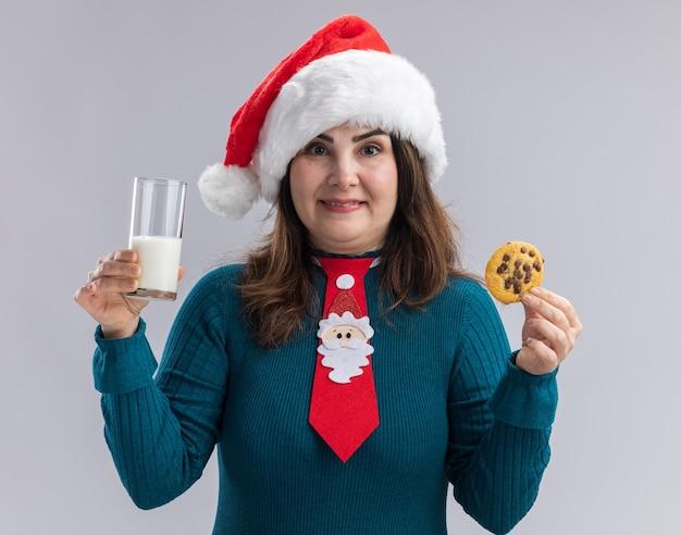 Felice donna caucasica adulta con cappello santa e cravatta santa tenendo un bicchiere di latte e cookie isolato su sfondo bianco con spazio di copia