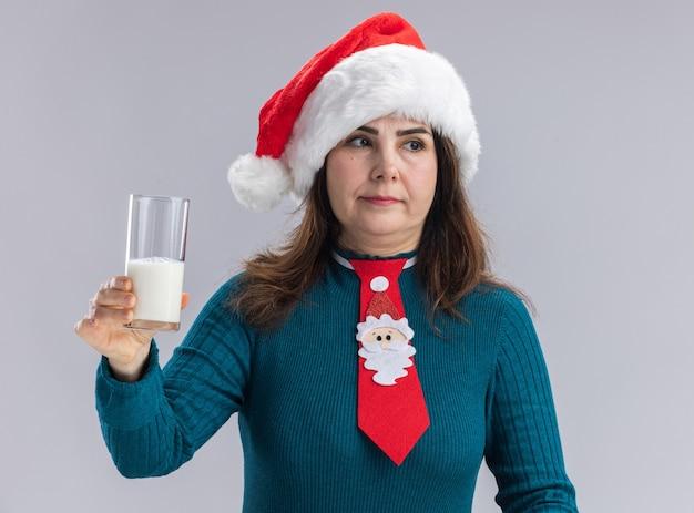 Donna caucasica adulta soddisfatta con cappello da babbo natale e cravatta di babbo natale che tiene in mano un bicchiere di latte guardando il lato isolato sul muro bianco con spazio di copia