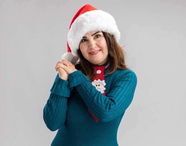 Pleased adult caucasian woman with santa hat and santa tie holding hands together isolated on white wall with copy space