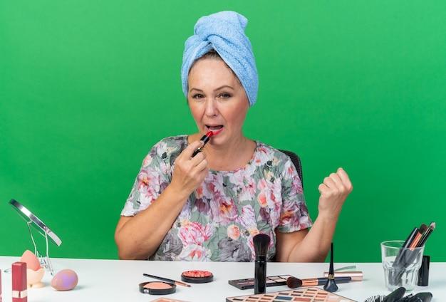 Довольная взрослая кавказская женщина с обернутыми волосами в полотенце сидит за столом с инструментами для макияжа, применяя помаду