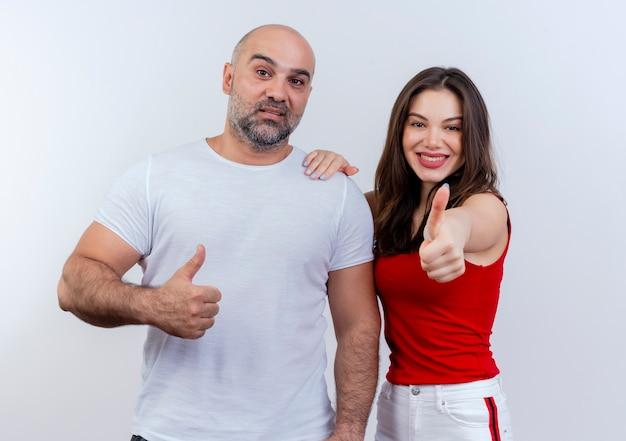 Piacevole coppia adulta alla ricerca e mostrando il pollice in su