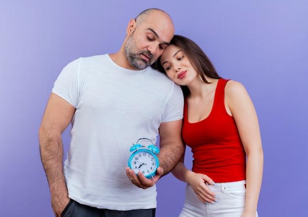 Felice coppia adulta uomo che tiene sveglia donna mettendo la testa sulla sua spalla sia guardando la sveglia