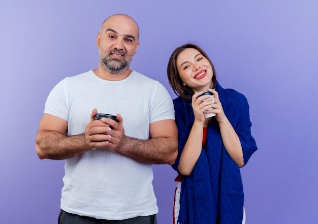 Felice coppia adulta donna avvolta in scialle sia tenendo in mano una tazza di caffè di plastica e guardando