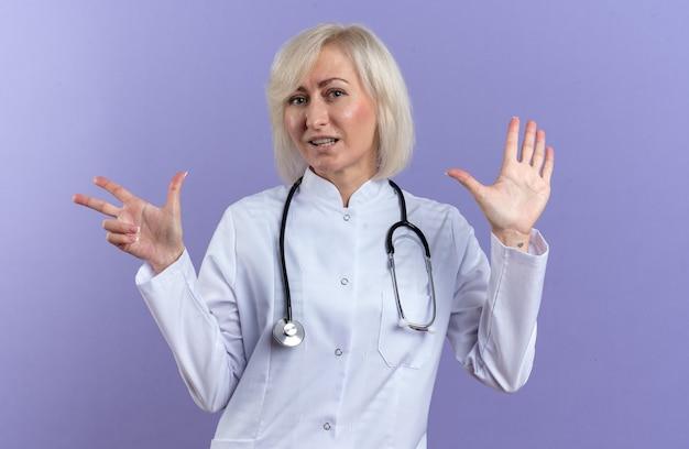 Compiaciuta dottoressa adulta in vestaglia medica con stetoscopio che gesturing otto con le dita isolate sulla parete viola con spazio copia