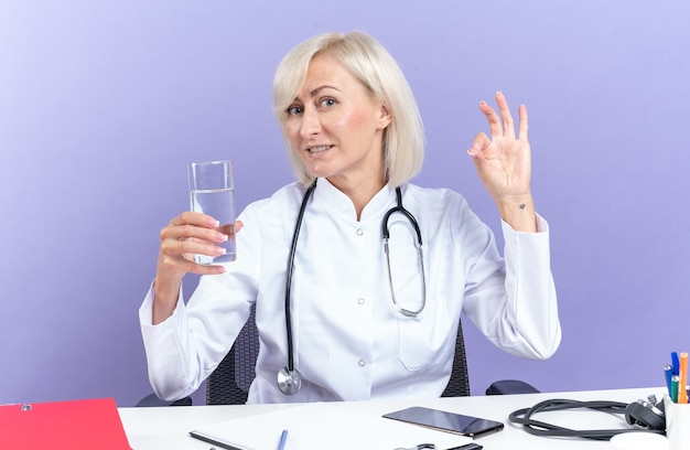 Compiaciuta dottoressa adulta in veste medica con stetoscopio seduto alla scrivania con strumenti da ufficio con in mano un bicchiere d'acqua e gesticolando segno ok isolato sul muro viola con spazio copia