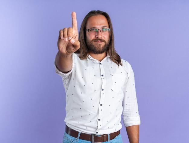 ジェスチャーを保持している眼鏡をかけている満足している大人のハンサムな男