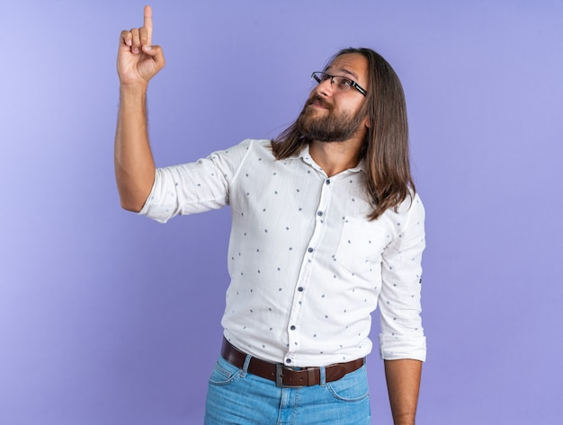 보라색 벽에 격리된 상태로 위를 바라보고 가리키는 안경을 쓴 성인 잘생긴 남자