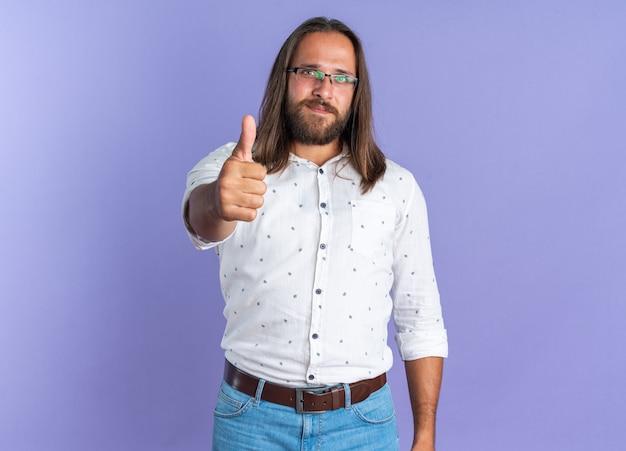 コピースペースと紫色の壁に分離された親指を示すカメラを見て眼鏡をかけて満足している大人のハンサムな男