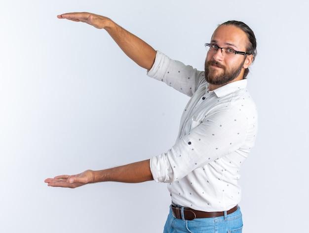 白い壁に分離されたカメラを見てサイズジェスチャーを行う縦断ビューで立っている眼鏡をかけて満足している大人のハンサムな男
