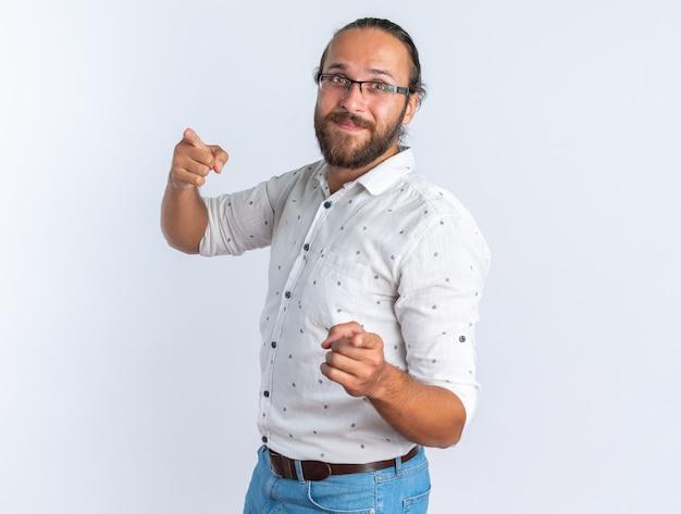 コピースペースで白い壁に隔離されたジェスチャーをしているカメラを見て縦断ビューで立っている眼鏡をかけて満足している大人のハンサムな男