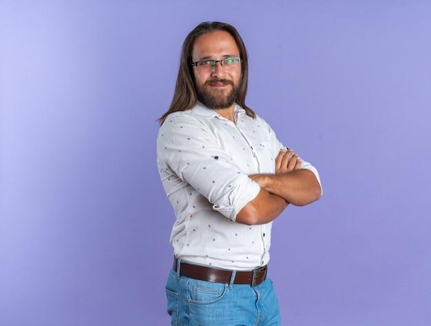 コピースペースと紫色の壁に分離されたカメラを見て閉じた姿勢で縦断ビューで立っている眼鏡をかけて満足している大人のハンサムな男